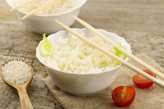 Plate of cooked long-grain rice on wooden background. Healthy eating, diet, vegetarianism. Royalty Free Stock Photos