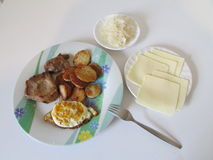 Plate with cooked potato, meat, egg next to plates with cheese and sauecraut.. stock photos