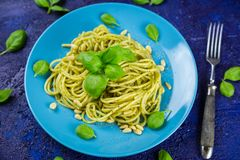 Plate of cooked spaghetti pasta with green pesto Royalty Free Stock Photos