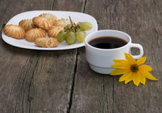 Plate with cookies, a cup of coffee and a yellow flower, a still Royalty Free Stock Image