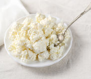 Plate of cottage cheese with a metal spoon on a white tablecloth. Stock Image