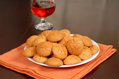A plate of crisp Amaretti cookies with snifter of Amaretto in ba Royalty Free Stock Photography