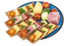 Plate of crisp bread with cheese, bacon, cucumbers and tomatoes Stock Image