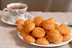 Plate of crisp Italian Amaretti cookies with a cup of hot tea in Stock Photo