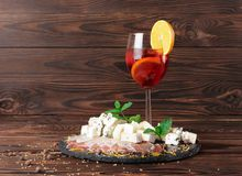 A glass of fruit beverage with orange and lemon, a plate of Roquefort and prosciutto on a wooden background. Royalty Free Stock Photography