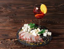 A glass of fruit beverage with orange and lemon, a plate of Roquefort and prosciutto on a wooden background. Royalty Free Stock Photo