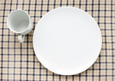 Plate and cup on tablecloth. White empty plate and cup on checked tablecloth Royalty Free Stock Photo