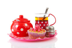 Plate with cup of tea and cupcake Stock Photos