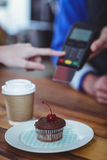 Plate of cupcake and coffee at counter Royalty Free Stock Photography