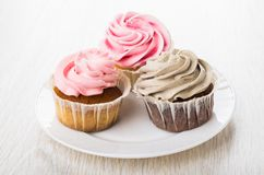 Plate of cupcakes with pink and brown cream on table. Plate of cupcakes with pink and brown cream on wooden table Royalty Free Stock Photo