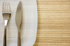 Plate and cutlery. On wood floor Stock Photo