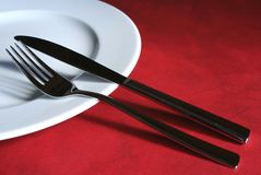 Plate and cutlery. White plate with silver cutlery on red background Stock Image