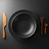 Plate and cutlery on a black table Stock Image
