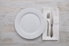 Plate, cutlery and cloth on wood. Colorful and crisp image of plate, cutlery and cloth on wood Royalty Free Stock Photography