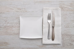 Plate, cutlery and cloth on wood Royalty Free Stock Photos