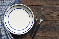 Plate and cutlery. Empty plate with blue stripes and cutlery on dark wooden table, top view Stock Image