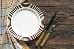 Plate and cutlery. Empty plate with brown stripes and cutlery on dark wooden table, top view Stock Image