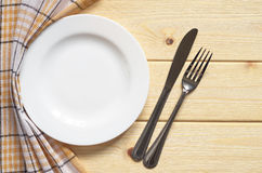 Plate and cutlery. Empty white plate and cutlery on wooden table, top view Royalty Free Stock Photo