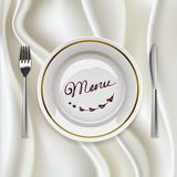 Plate with cutlery on glossy tablecloth Royalty Free Stock Photography