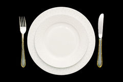 Plate and cutlery. Isolated, black background Royalty Free Stock Images