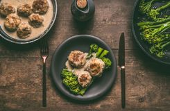 Plate with cutlery and low carb dieting meal: meat balls and blanched broccoli on wooden table background. Top view with copy space. Healthy weight loss diet royalty free stock images