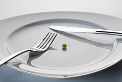 Plate with cutlery and a pea. Plate with cutlery and a single pea Royalty Free Stock Photos