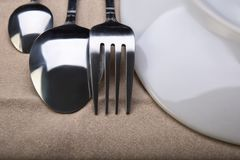 Plate and Cutlery on the tablecloth. Shooting in the Studio .Fork,spoon and a small spoon lying on the light brown tablecloth next to a plate.The view from the Royalty Free Stock Image