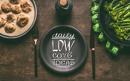 Plate with cutlery and text lettering: Daily low carb ideas on wooden background with meat balls, broccoli and measure tape stock photography