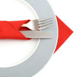 Plate and cutlery on white. Plate and cutlery with red fabric napkins, on white background Stock Photography