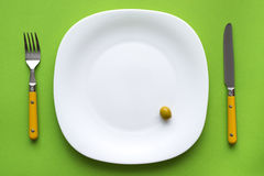 Plate and cutlery. White plate with one olive and cutlery on green tablecloth Stock Photography
