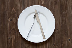 Plate and cutlery on wooden background in dislike form. Top view Royalty Free Stock Image