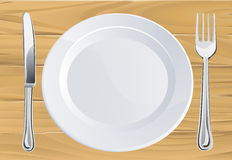 Plate and cutlery on wooden table Royalty Free Stock Photos