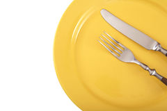 Plate and cutlery. Cutlery and yellow plate isolated on a white background stock photos