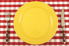 Plate and cutlery. Cutlery and yellow plate on a tablecloth Royalty Free Stock Photography
