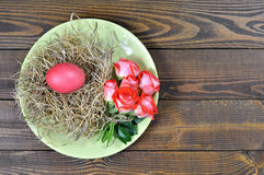 Plate decorated with Easter egg in the nest and flowers Royalty Free Stock Images