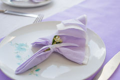 Plate decoration with napkins and linden flower. Plate decoration with violet napkin and linden flower. Table decoration idea stock photo