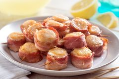 A plate of delicious bacon wrapped scallops. With lemon stock photography