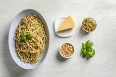 Plate of delicious basil pesto pasta with ingredients stock image