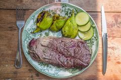 Plate with delicious beef steak, figs and zucchinis royalty free stock photos