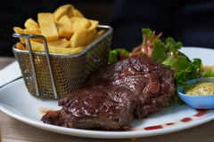 A plate of delicious beef steak and french fries. On the table stock image