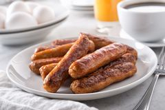 Breakfast Sausage. A plate of delicious cooked breakfast sausage with coffee, orange juice and eggs royalty free stock images