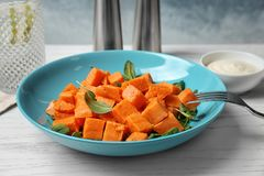 Plate with delicious cut sweet potato. On table stock photography