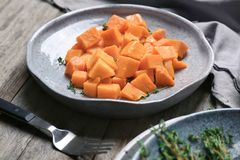Plate with delicious cut sweet potato. On table royalty free stock image