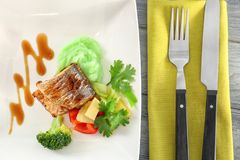 Plate with delicious fish, sauce, vegetables and cutlery Royalty Free Stock Photo