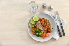Plate with delicious fish, sauce and vegetables Stock Photo