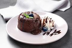 Plate of delicious fresh fondant with hot chocolate. And blueberries on table. Lava cake recipe Stock Photos