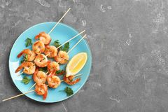 Plate with delicious fried shrimp skewers and lemon royalty free stock image