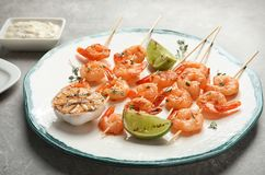 Plate with delicious fried shrimp skewers and lime on grey table royalty free stock photos