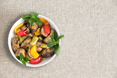 Plate of delicious grilled fresh vegetables. Prepared Turkish style with eggplant, zucchini and red and yellow sweet peppers, over head view on a beige cloth Royalty Free Stock Image
