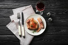Plate with delicious grilled steak and glass of red wine on table stock photography